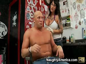 Tattooed chick with huge boobs fucks in a tattoo parlor